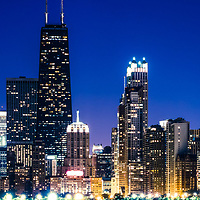 Chicago panorama skyline at night with blue tone. Includes Chicago downtown city buildings and the famous John Hancock Center building. The John Hancock Center is one of the world's tallest skyscrapers and is a popular fixture in the Chicago skyline. Photo panoramic ratio is 1:3.