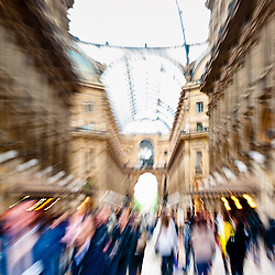 Intentionally motion blurred creative image of commuters walking in Galleria Vittorio Emanuele II in Milan, Italy