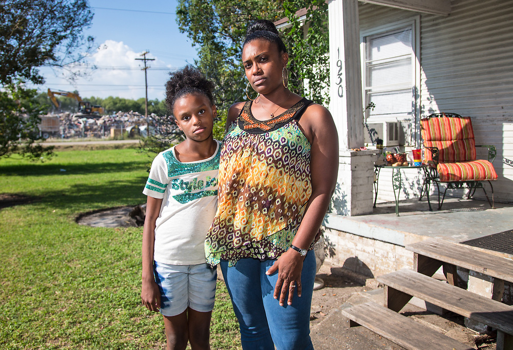 Tami Thomas-Pinkney with her daughter Trinity Handy on their front lawn in Port Arthur, Texas, across from one of the city's temporary dumpsites.
