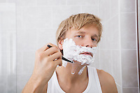 Portrait of mid-adult man shaving in bathroom