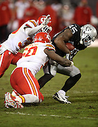 Kansas City Chiefs outside linebacker Justin Houston (50) tackles Oakland Raiders fullback Marcel Reece (45) during the NFL week 12 regular season football game against the Oakland Raiders on Thursday, Nov. 20, 2014 in Oakland, Calif. The Raiders won their first game of the season 24-20. ©Paul Anthony Spinelli