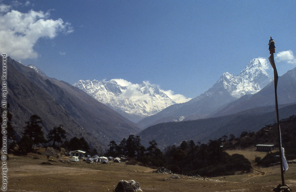 View from Tengboche Monastery toward Mt. Everest. Everest is the triangular peak visible with the snow plume, just visible above the Nuptse-Lhotse wall. The tents in the foreground belong to a group of New Zealanders, including Sir Edmund Hillary, who was at Tengboche constructing a new school. Ama Dablam is the peak on the right side of the photo.