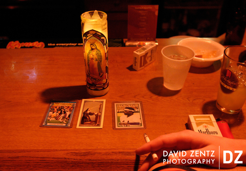 DAVID ZENTZ/Journal Star.Bears fan Paul Guse sits by a candle of the Virgin of Guadalupe and Walter Payton collectors cards he brought for good luck while watching Superbowl XLI at Gorman's Pub Sunday night.
