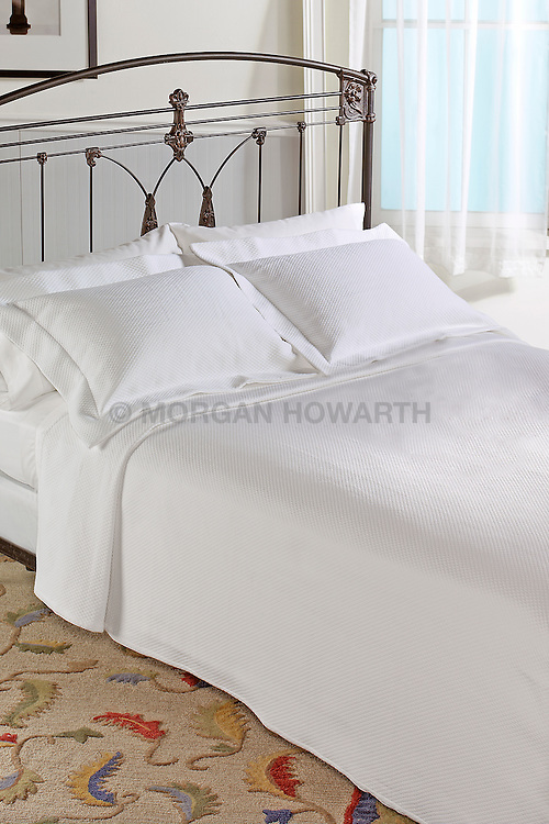 Cast iron bed with white linens