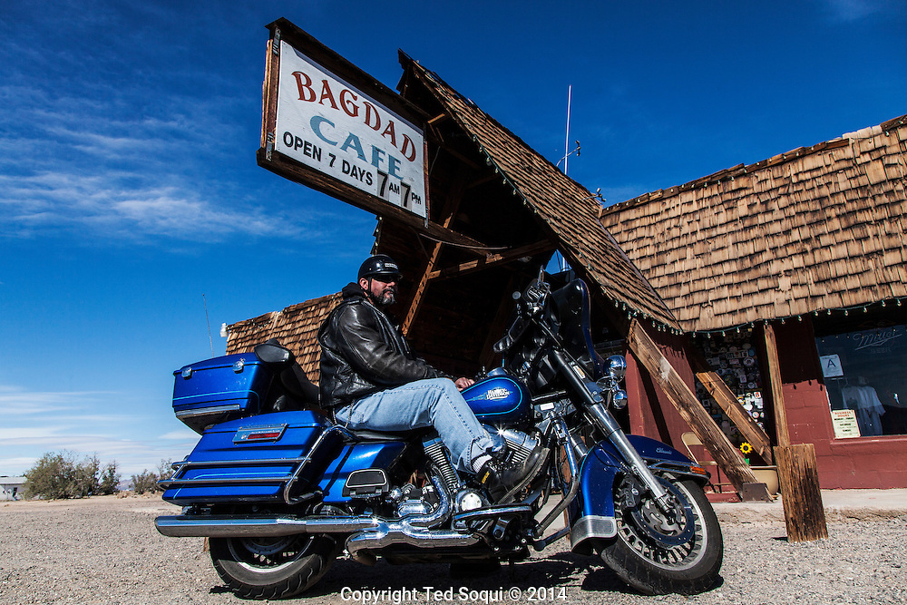 A biker sits out front of the Bagdad Cafe.<br /> U.S. Route 66, also known as the Mother Road, in the Mojave desert of California. The two major connector cites in the Mojave desert are Barstow and Amboy. U.S. Route 66 was the first major east west highway for the US, starting in Chicago, Il and ending in Santa Monica, CA. The 2,448 mile long highway was built in November 11,1926. Most of Route 66 has been decommissioned, but there are several parts that are now historically preserved.