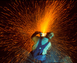 Stock photo of sparks flying from a man operating a metal grinder