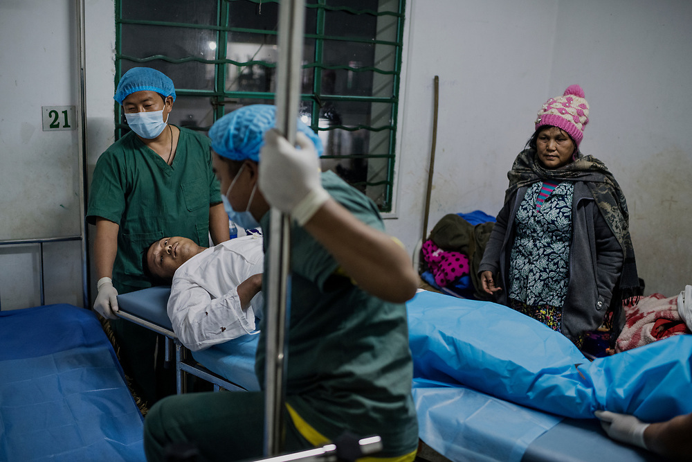 Mai Ja Yang, Myanmar 20180117 <br /> Corporal Labang Lum Mai, 31, was hit by shrapnel on December 18. The metal hit his leg and broke it during clashes with the Myanmar Army. His mother Mahka Roi Tawng, 57, is visiting at the Mai Ja Yang hospital as Lum Mai is rolled out from surgery. He says he wants to get back to the fighting when he gets better. &ndash; I have been in combat before, but never this intense, they attacked us with grenades, airplane bombing and troops on the ground. I saw my friends die, he says.<br /> Photo: Vilhelm Stokstad / Kontinent
