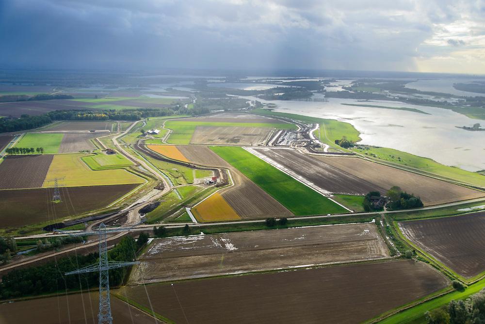 Nederland, Noord-Brabant, Werkendam, 23-10-2013; Ruimte voor de Rivier project Ontpoldering Noordwaard. Het deel rechtsboven is reeds ontpolderd, onder het gedeelte in ontwikkeling waar boerderijen en particuliere huizen op nieuw opgeworpen terpen gebouwd worden. Midden in beeld een nieuwe dijk, hierlangs zal het water stromen, vanaf rivier de Nieuwe Merwede , de bestaande dijk krijgt een instroom opening.<br /> Delen van de polder (links) wordt ontpolderd en de dijken worden verlegd en/of verlaagd waardoor bij hoogwater het rivierwater ook door de polder sneller weg kan stromen richting zee. Gevolg van de ingrepen is ook dat de waterstand verder stroomopwaarts zal dalen.<br /> National Project Ruimte voor de Rivier (Room for the River) By lowering and / or moving the dike of the Noordwaard polder the area will become subject to controlled inundation and function as a dedicated water detention district. Houses and farmhouses will be constructed on new dwelling mounds. <br /> luchtfoto (toeslag op standard tarieven);<br /> aerial photo (additional fee required);<br /> copyright foto/photo Siebe Swart
