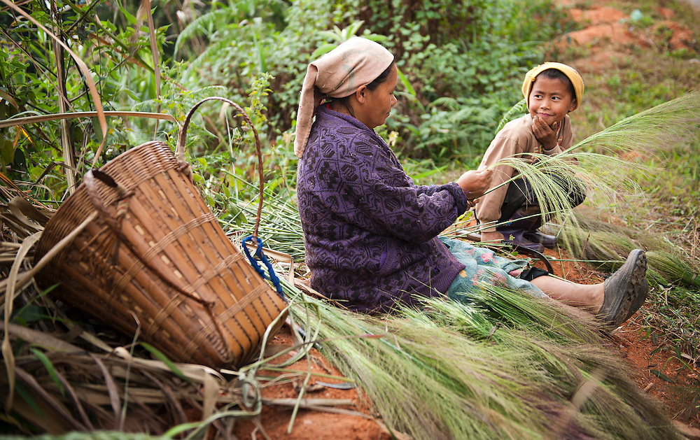 A Khamu mother and son prepair grass to make into brooms, Laos.