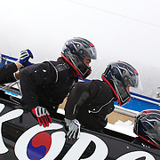 "Winter Olympics, Vancouver, 2010.The Korean team load into the bobsleigh during the Bobsleigh Four-man competition  at The Whistler Sliding Centre, Whistler, during the Vancouver Winter Olympics. 25th February 2010. Photo Tim Clayton..'BOB'..Images from the Four-man Bobsleigh Competition. Winter Olympics, Vancouver 2010..History was made at the Whistler Sliding Centre when the USA four-man bobsleigh team, led by Steven Holcomb took the Gold. The first time since 1948, a gap of 62 years, since the USA have won an Olympic Bobsleigh gold and they did it with their sleigh named ""Night Train""...The four days of practice and competition show the tension, nervousness and preparation as the teams of hardened men cope with the challenge of traveling at average speeds of over 150 km an hour. Indeed, five teams had already pulled out of the event before the opening heats because of track complexity, speed and fear, and on the final day, another four teams did not start after six crashes in the first two heats...Teams warm up behind the start complex, warming muscles in the cold in preparation for the explosive start. Many teams prepare in silence, mentally preparing themselves as they wait at the top of the run, in the bobsleigh sheds and the loading areas for their turn. When it's time to slide each team performs it's own starting ritual, followed by the much practiced start out of the blocks for just over four seconds, the teams are then in the hands of the accomplished drivers as they hurtle down the track for just over fifty seconds...Spectators clamber for the best position on track to see the sleighs for a split second, many unsuccessfully try to capture the moments on camera, The rumble of the sleigh is heard then the crowds gasp as it hurtles past in a blur...The American foursome of  Steven Holcomb, Justin Olsen, Steve Mesler and Curtis Tomasevicz finished with a pooled four-heat time of 3min 24.46sec. The German team led by Andre Lange won the Silver Medal in a combi"