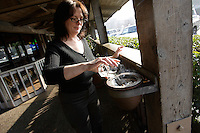 BELMONT, CA- JANUARY 24: Lori DeMars pours water on a burning cigarette in an ashtray outside Hola! Mexican Restaurant on January 25, 2007 in Belmont, California.  (Photograph by David Paul Morris)