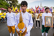 05 MAY 2104 - BANGKOK, THAILAND:  People in traditional Thai outfits prepare to make merit by honoring the Thai Monarchy on Coronation Day in Bangkok. Thousands of Thais packed the area around Sanam Luang and the Grand Palace Monday evening for a special ceremony to mark Coronation Day, which honored the 64th anniversary of the coronation of Bhumibol Adulyadej, the King of Thailand. Many of the people also support the anti-government movement led by Suthep Thaugsuban. Most of the anti-government protesters are conservative supporters of the monarchy.   PHOTO BY JACK KURTZ
