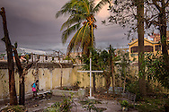A young woman walks to the water well (to the left of the cross) amongst fallen debris from Hurricane Matthew in the entranceway to First Lutheran Church of Les Cayes on Tuesday, Oct. 11, 2016, in Haiti.  LCMS Communications/Erik M. Lunsford