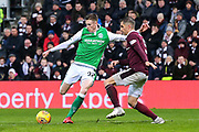 Oli Shaw (#32) of Hibernian hits a shot as Aaron Hughes (#5) of Heart of Midlothian attempts to block during the William Hill Scottish Cup 4th round match between Heart of Midlothian and Hibernian at Tynecastle Stadium, Gorgie, Scotland on 21 January 2018. Photo by Craig Doyle.
