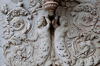 Milan, Italy, Duomo Cathedral. Stone frieze of Mermen carrying baskets on their heads and their tails flow into plant forms.