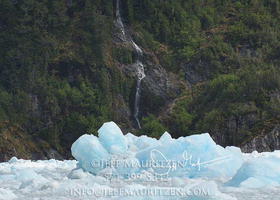 Glacial ice and a waterfall in Garibaldi fjord in Parque Nacional Alberto de Agostini, Chile.