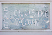 A closing down sale window is written on smeared whitewashed glass on a former village shop.