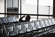 HUNTSVILLE, AL – APRIL 2, 2014: A passenger waits for his flight in the only concourse at Huntsville International Airport. In an attempt to reverse the trend of declining service by airlines in small airports, Huntsville International Airport attempted to implement a rebate plan that would offer incentives to some carriers for enhanced service to the midsize city. The Federal Aviation Administration cautioned that the plan could potentially violate a federal law barring interference with airline fares, routes or service levels. When the industry's largest trade group, Airlines for America, threatened to, the airport's plan was disrupted. As major airlines continue to trim service offerings in smaller, less profitable cities, airports like Huntsville International struggle to attract and maintain carriers. CREDIT: Bob Miller for The Wall Street Journal<br />
