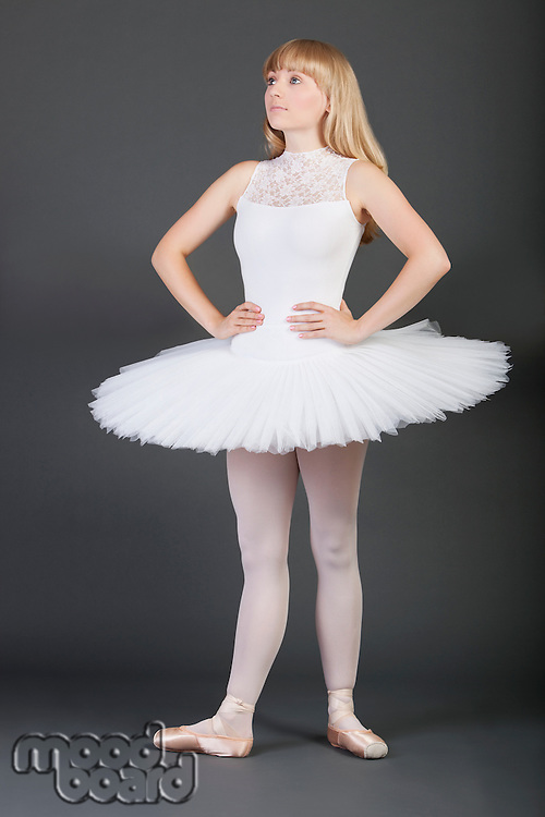 Young female ballet dancer with hands on hips standing over grey background