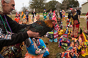 A home owner shows off a live chicken to costumed revelers before letting it go during the Faquetigue Courir de Mardi Gras chicken run on Fat Tuesday February 17, 2015 in Eunice, Louisiana. The traditional Cajun Mardi Gras involves costumed revelers competing to catch a live chicken as they move from house to house throughout the rural community.