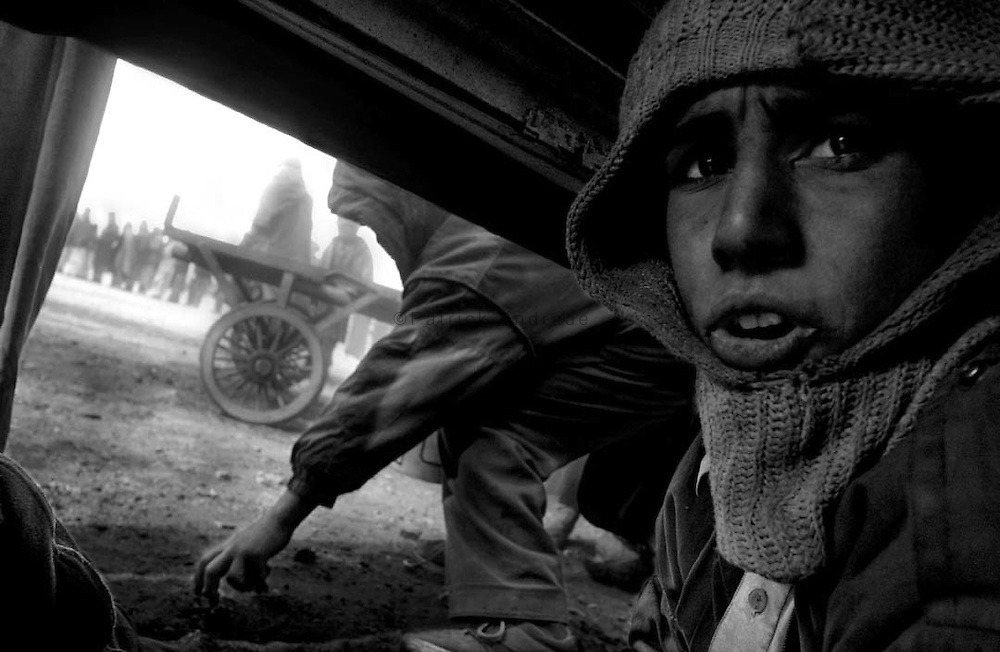 <<coal distribution photo package>>..A young boy crouches beneath a truck to scrounge for scraps of coal as it is unloaded by the ICRC (International Committe for the Red Cross) inside Kabul city. (shot 2-11-02)