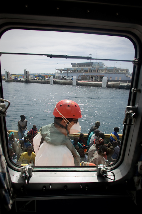 A marine rescue worker and some of the 78 would-be immigrants are seen through the coastguard boat window. The cayuco was intercepted 80 miles away from the coast of Tenerife, in the Canary Islands, Spain, Wednesday, Oct. 24, 2007. Thousands of people try to reach Europe through Spain each year, an increasing number of them coming from Mauritania and Moroccan-controlled Western Sahara. Mauritania's Red Crescent says more than 1,000 people have died trying to reach Spain since the beginning of the year.
