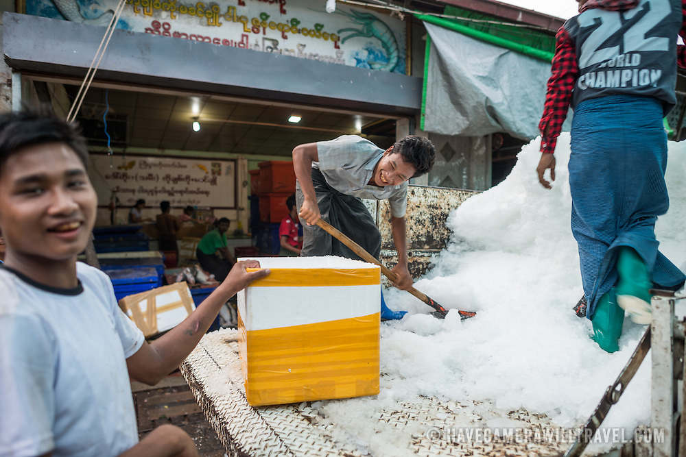 Men shovel ice to deliver to the fish vendors at the fish and flower market in Mandalay, Myanmar (Burma).