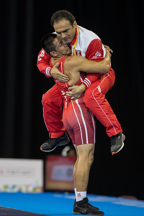 Mario Molina of Peru hugs his coach Enrique Cubas Ypanaque following his win over Jefrin Mejia of Honduras in the bronze medal match for the  66kg class of the men's greco-roman wrestling at the 2015 Pan American Games in Toronto, Canada, July 15,  2015.  AFP PHOTO/GEOFF ROBINS