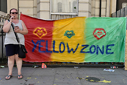 © Licensed to London News Pictures. 27/08/2017. London, UK. A sign supporting the victims of the Grenfell Tower fire is seen as members of the public enjoy Family Day at the Notting Hill Carnival.  Over one million revellers are expected to attend Europe's biggest street party which takes place over the Bank Holiday Weekend. Photo credit : Stephen Chung/LNP