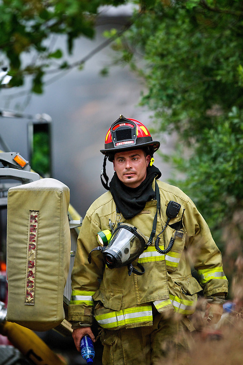 Kootenai County Fire Lt. Justin Capaul walks away from the scene of a garage fire in a lakefront home Thursday on Lake Coeur d'Alene.