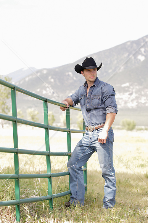 hot cowboy leaning on a gate