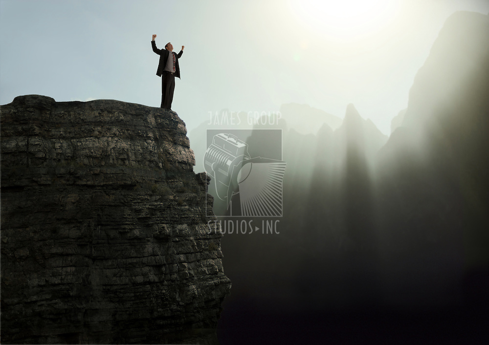 Businessman standing with arms raised in elation on the top of a mountain peak