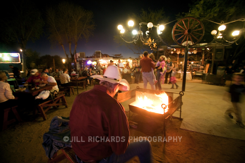 A lone cowboy stokes the fire at Greasewood Flat, an outdoor restaurant, bar and dance hall located in Scottsdale, Arizona.
