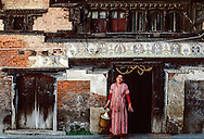 A woman in front of the doorstep of her centuries old home.