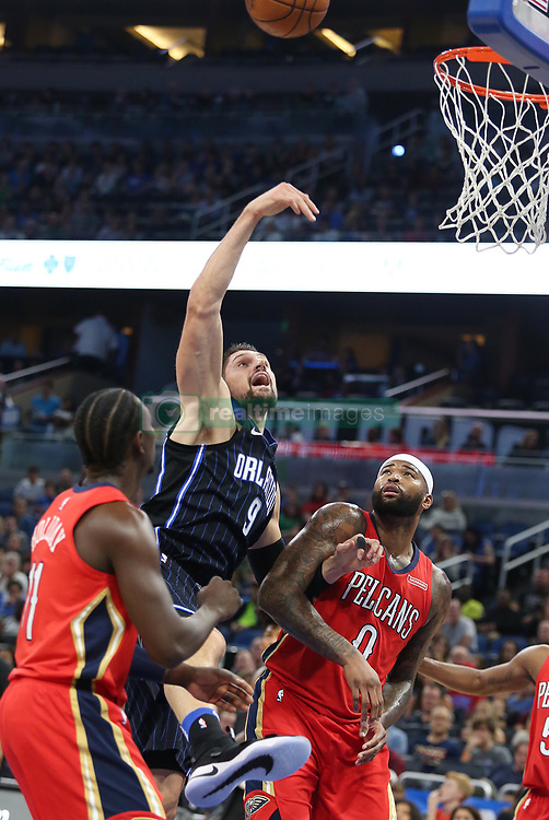 December 22, 2017 - Orlando, FL, USA - The Orlando Magic's Nikola Vucevic (9) scores between the New Orleans Pelicans' Jrue Holiday (11) and DeMarcus Cousins (0) at the Amway Center in Orlando, Fla., on Friday, Dec. 22, 2017. (Credit Image: © Stephen M. Dowell/TNS via ZUMA Wire)