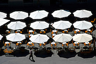 Umbrellas are suspended on the deep shadows cast on a public square in the Slovenian capital