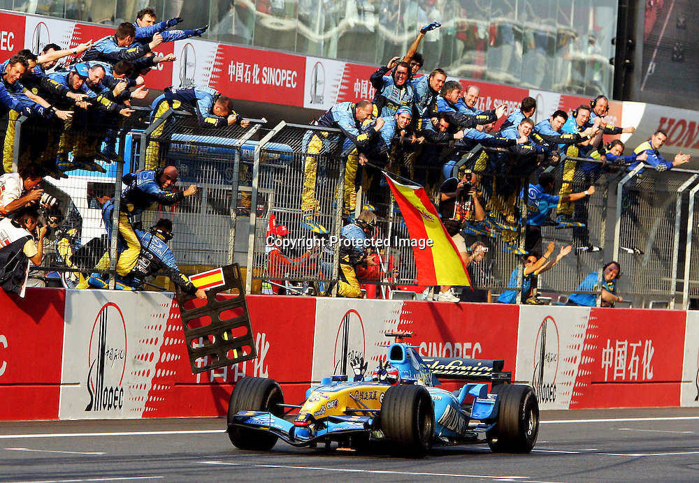 epa00554014 Spanish Formula One driver Fernando Alonso of Renault drives past mechanics and celebrates his victory in the Chinese Grand Prix at the Chinese F1 track near Shanghai, China, Sunday 16 October 2005.  EPA/KERIM OKTEN