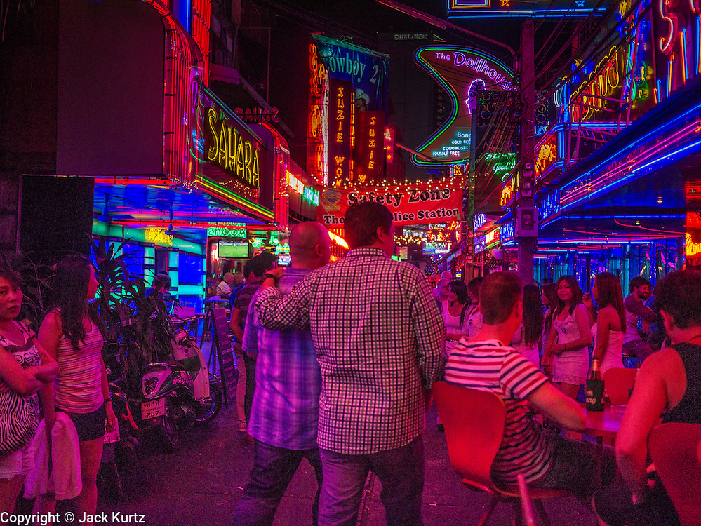 "05 JANUARY 2013 - BANGKOK, THAILAND: Men walk through ""Soi Cowboy,"" a red light district lined with go-go bars and brothels, in Bangkok. Prostitution in Thailand is technically illegal, although in practice it is tolerated and partly regulated. Prostitution is practiced openly throughout the country. The number of prostitutes is difficult to determine, estimates vary widely. Since the Vietnam War, Thailand has gained international notoriety among travelers from many countries as a sex tourism destination. One estimate published in 2003 placed the trade at US$ 4.3 billion per year or about three percent of the Thai economy. It has been suggested that at least 10% of tourist dollars may be spent on the sex trade. According to a 2001 report by the World Health Organisation: ""There are between 150,000 and 200,000 sex workers (in Thailand).""      PHOTO BY JACK KURTZ"