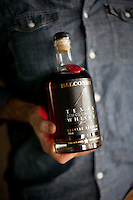 1-7-13---- Balcones Distillery owner Chip Tate holds a bottle of Balcones whisky outside the distillery in Waco, Texas.
