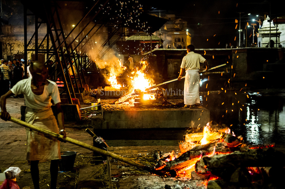 5th May 2015, Kathmandu, Nepal.  Cremation workers on the ghats attending pyres of earthquake victims at the Pashupatinath Temple on the 5th May 2015, Kathmandu, Nepal.<br /> <br /> The Pashupatinath Temple is a famous, sacred Hindu temple dedicated to Pashupatinath is located on the banks of the Bagmati River 5 kilometres north-east of Kathmandu Valley in the eastern city of Kathmandu the capital of Nepal. This temple is considered one of the sacred temples of Hindu faith .The temple serves as the seat of the national deity, Lord Pashupatinath. This temple complex is on UNESCO World Heritage Sites's list Since 1979.This &quot;extensive Hindu temple precinct&quot; is a &quot;sprawling collection of temples, ashrams, images and inscriptions raised over the centuries along the banks of the sacred Bagmati river&quot; and is included as one of the seven monument groups in UNESCO's designation of Kathmandu Valley as a cultural heritage site. The temple is one of the 275 Paadal Petra Sthalams (Holy Abodes of Shiva) on the continent. Kotirudra Samhita, Chapter 11 on the Shivalingas of the North, in Shiva Purana mentions this Shivalinga as the bestower of all wishes. One of the major Festivals of the temple is Maha Shivaratri on which day over 700,000 devotees visit here.<br /> <br /> An earthquake with magnitude 7.8 occurred near Lamjung, Nepal, 50 miles northeast of the capital Kathmandu at 06:11:26 UTC on Apr 25, 2015. The capital has seen considerable devastation including the nine-story Dharahara Tower, one of Kathmandu's landmarks built by Nepal's royal rulers as a watchtower in the 1800s and a UNESCO-recognised historical monument. It was reduced to rubble and there were reports of people trapped. Portions of historic buildings in the World Heritage gazetted site of Patan have also been destroyed as well as many buildings in the old city. <br /> <br /> PHOTOGRAPH BY AND COPYRIGHT OF SIMON DE TREY-WHITE<br /> <br /> + 91 98103 99809<br /> email: simon@simondetreywhite.com<br /> photographer in delhi