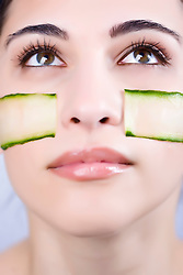 Close up of a young woman with cucumber slices on her cheeks