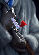 A lady clutches the universal reminder of Veterans Day, a red poppy, at the Veterans Day ceremony held in Garden City.  (November 11,  2013). © Audrey C. Tiernan