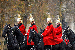 © Licensed to London News Pictures. 10/12/2017. London, UK. Members of the Household Cavalry march down The Mall as snow falls over Horse Guards Parade in London on Sunday, 10 December 2017. Photo credit: Tolga Akmen/LNP