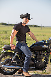 hot cowboy sitting on a motorcycle