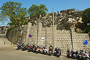 Macau, China - September 11, 2013: Exterior wall of the Guia Fortress with motorbikes parking at Caminho dos Artilheiros street in Macau, China.