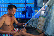 09 MAY 2013 - BANGKOK, THAILAND: A fisherman who is a Yellow Shirt repairs his nets during a protest affiliated with the Yellow Shirts on Sanam Luang in Bangkok. The protesters were supporting the revet ousted  PHOTO BY JACK KURTZ