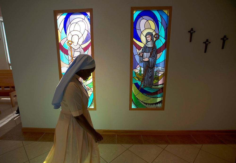 A nun walks past two stained glass windows Monday, April 8, 2013 at the Benedictine Sisters of Florida's Priory and Chapel in Dade City. These windows along with the pews and other items from the chapel will be used in a new chapel. Saint Leo University recently purchased the buildings and the sisters plan to build a new facility.