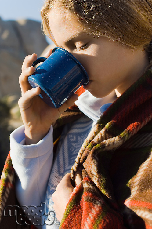 Young Woman Drinking from Cup and Clutching Blanket