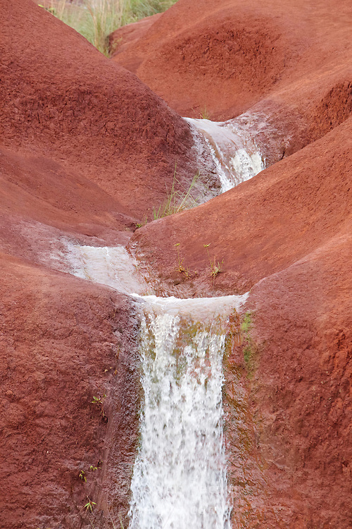 Series of small waterfalls carved out of red dirt in Waimea Canyon, on the island of Kauai, Hawaii.