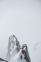 A pair of mountaineers as seen during the traverse of a rock feature on a ridge of Aiguilles Marbrées on a cold and cloudy Winter day in Mont Blanc Massif.